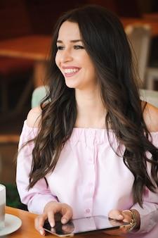 Piękny młodej kobiety obsiadanie w kawiarni pije kawową herbatę