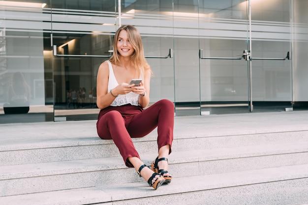 Piękny młodej kobiety obsiadanie w schodkach na telefonie komórkowym