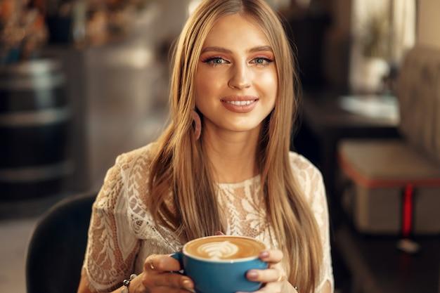 Piękny młodej kobiety obsiadanie w sklep z kawą cieszy się jej napój