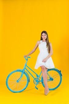 Piękny młodej kobiety pozować sadzam na błękitnym bicyklu