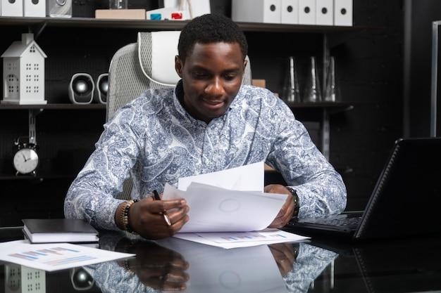 Piękny młody amerykanina afrykańskiego pochodzenia biznesmen pracuje z dokumentami i laptopem w biurze