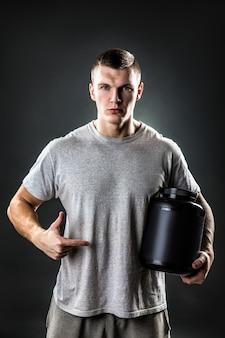 Piękny młody atletyczny mężczyzna trzyma słój sporta odżywianie