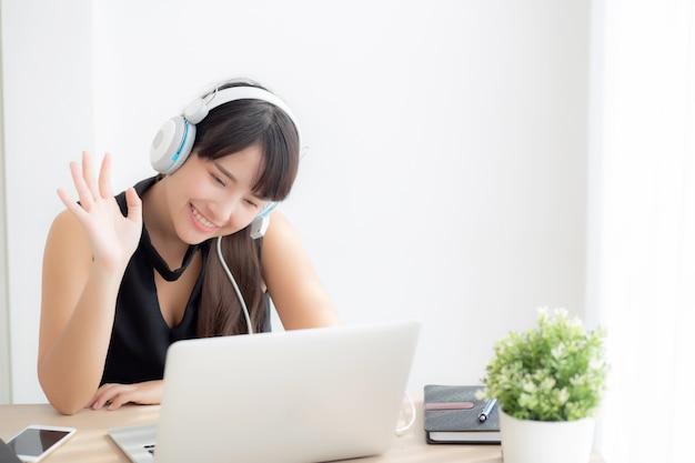 Piękny młody azjatykci kobiety odzieży hełmofon mówi cześć używać rozmowy wideo rozmowę na laptopie