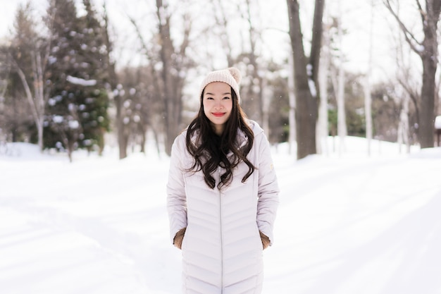 Piękny młody azjatykci kobiety ono uśmiecha się szczęśliwy dla podróży w śnieżnym zima sezonie