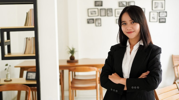Piękny młody biznes azjatycki kobieta w garniturze stojący w kawiarni