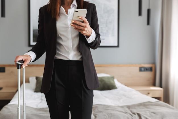 Piękny młody biznes kobieta w wizytowym ubrania w pomieszczeniu w domu z walizką przy użyciu telefonu komórkowego.