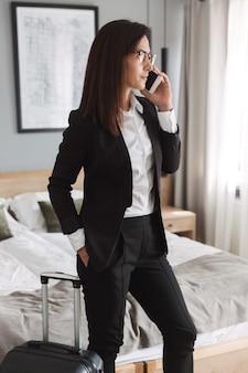 Piękny młody biznes kobieta w wizytowym ubrania w pomieszczeniu w domu z walizką rozmawia przez telefon komórkowy.
