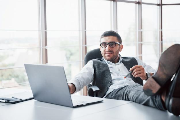 Piękny młody biznesmen trzyma jego w okularach trzyma jego nogi na stole patrzeje laptop w biurze