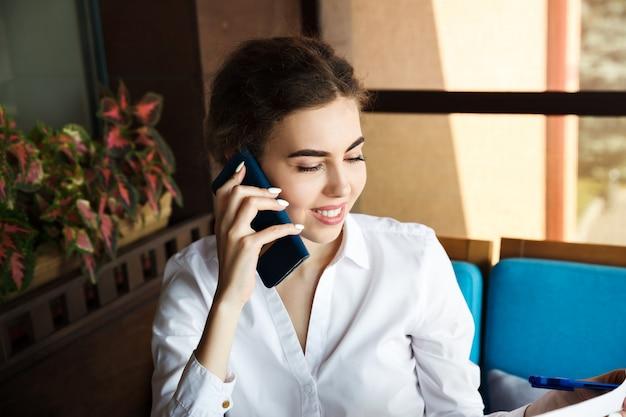 Piękny młody bizneswoman opowiada na telefonie w kawiarni