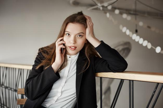 Piękny młody bizneswoman opowiada telefonem w kawiarni