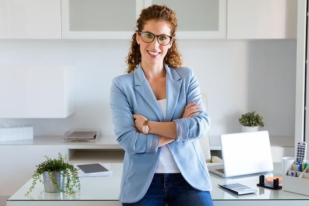 Piękny młody bizneswoman patrzeje kamerę w biurze.