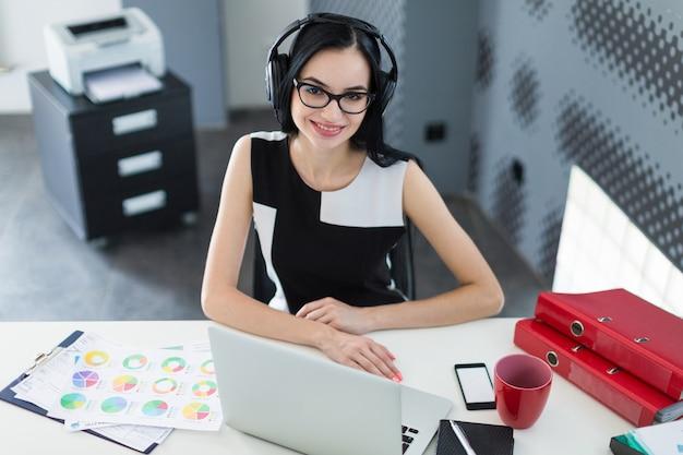 Piękny młody bizneswoman w czerni sukni, hełmofonach i szkłach, siedzi przy stołem i pracuje na laptopie