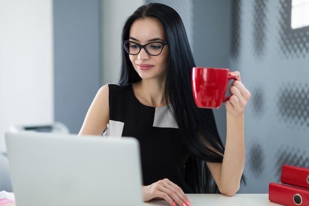 Piękny młody bizneswoman w czerni sukni i szkłach siedzi przy stołem i pracuje z kawą w ręce