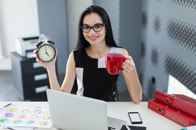 Piękny młody bizneswoman w czerni sukni i szkłach siedzi przy stołem i pracuje z laptopem, trzyma filiżankę i budzika