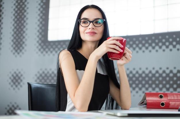 Piękny młody bizneswoman w czerni sukni i szkłach siedzi przy stołem i trzyma czerwoną filiżankę