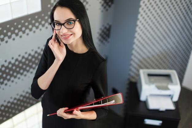 Piękny młody bizneswoman w czerni sukni i szkłach trzyma papierową falcówkę