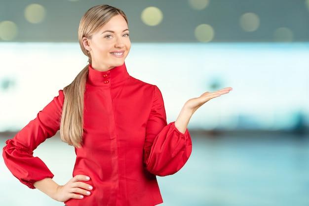 Piękny młody bizneswoman wskazuje przy kopii przestrzenią odizolowywającą