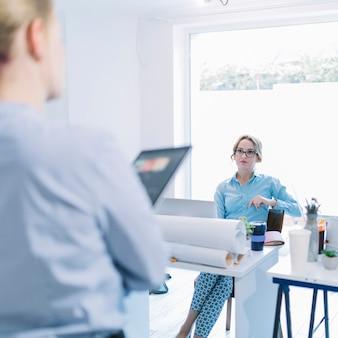 Piękny młody bizneswomanu obsiadanie na krześle słucha jej kolega w spotkaniu