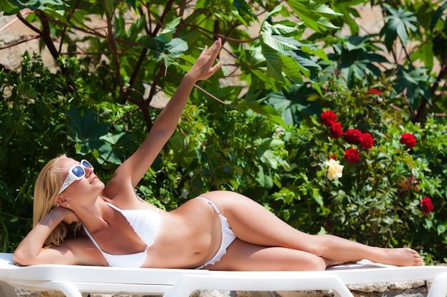 Piękny młody blond kobiety lying on the beach dalej sunbed i cieszący się światło słoneczne