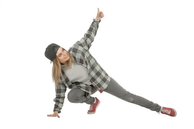 Piękny młody blond taniec hip-hop i pokazuje kciuki do góry na białym tle