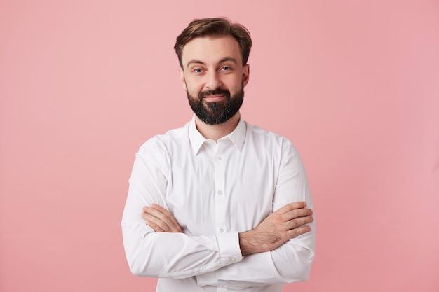 Piękny młody brunetka mężczyzna z brodą, patrząc z przodu z uroczym pozytywnym uśmiechem, ubrany w formalne ubrania, stojąc przed różową ścianą z założonymi rękami