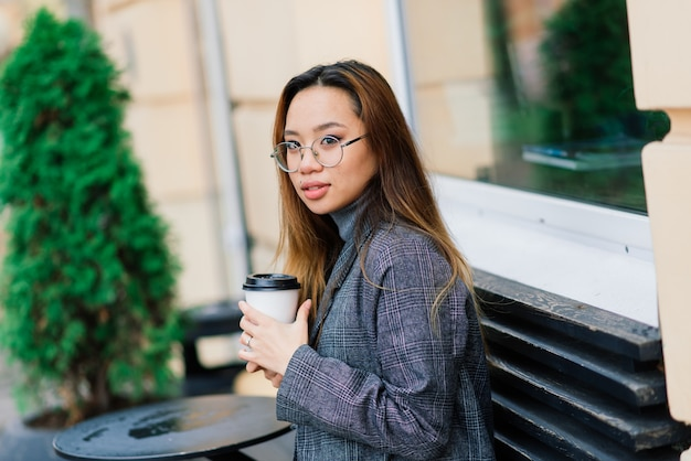 Piękny młody chiński student trzymając filiżankę kawy na ulicy