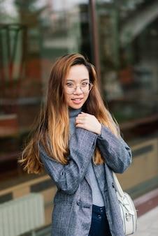 Piękny młody chiński student trzymając książkę na ulicy