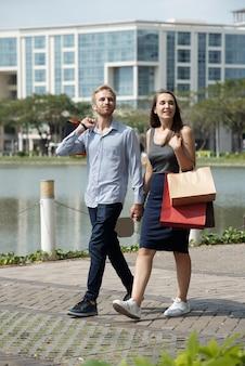 Piękny młody chłopak i zakochana dziewczyna niosący torby na zakupy podczas spaceru po mieście po słońcu...