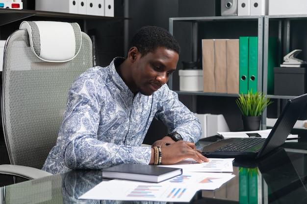 Piękny młody czarny biznesmen pracuje z dokumentami i laptopem w biurze