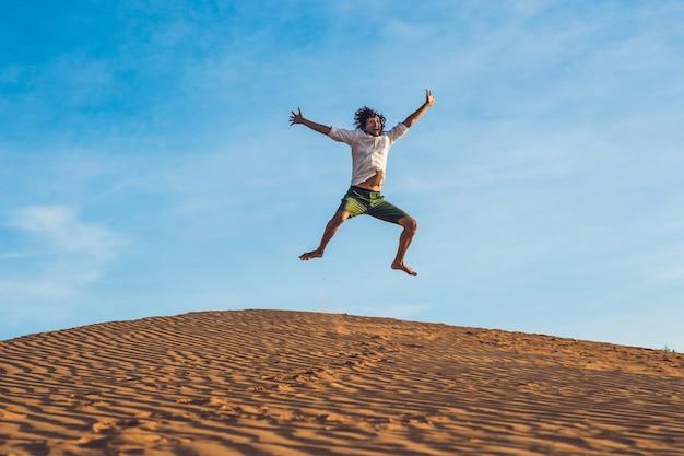 Piękny młody człowiek skoki boso na piasku na pustyni z przyrodą i słońcem. zabawa, radość i wolność.