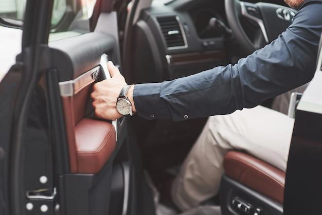Piękny młody człowiek w pełnym garniturze podczas prowadzenia samochodu.