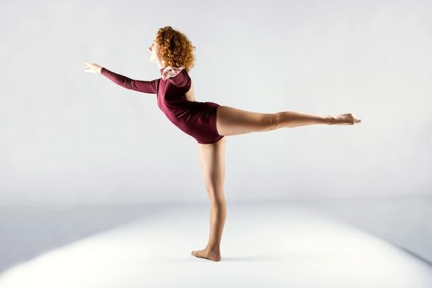 Piękny młody fachowy tancerz tanczy nad białym tłem.