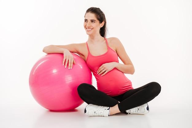Piękny młody kobieta w ciąży obsiadanie z fitball i patrzeć daleko od