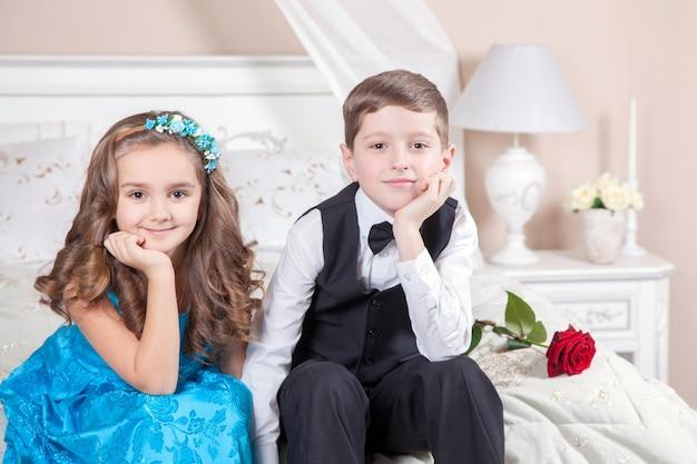 Piękny młody książę w smokingu i księżniczka trzymając różę w niebieska sukienka i zespół mody pozowanie, siedząc na łóżku w jasnym pokoju i patrząc w dal. historia miłosna. strzał studio.