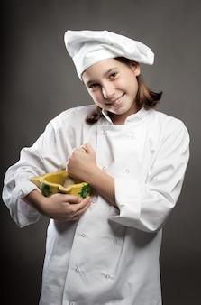 Piękny młody kucharz trzyma moździerz na szarej ścianie