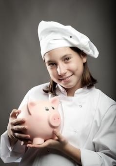 Piękny młody kucharz trzyma skarbonkę