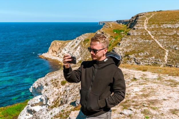 Piękny młody mężczyzna cieszy się malowniczym krajobrazem morskim z lazurową wodą na zachodnim wybrzeżu krymu