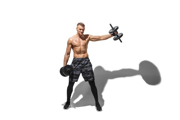 Piękny młody mężczyzna sportowiec ćwiczący na białym tle studio z cieniami