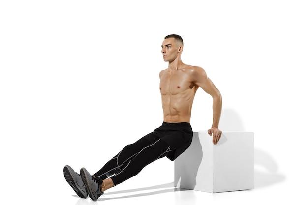Piękny młody mężczyzna sportowiec ćwiczący na białym z cieniami
