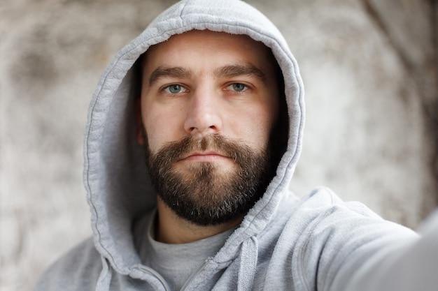 Piękny młody mężczyzna z brodą w kraciastej koszuli robi siebie, uśmiechnięty, na szarym tle