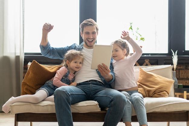 Piękny młody ojciec, jego śliczne córeczki używają tabletu i uśmiechają się, siedząc na kanapie w domu.