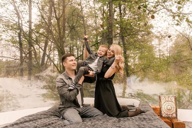Piękny młody rodzinny mężczyzna kobieta i syn relaksują się w lesie na łonie natury w dużym okrągłym namiocie z łóżkiem i kuchenką do gotowania, pikniku, kempingu
