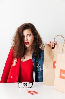 Piękny młody sprzedaży kobiety obsiadanie z papierowymi torba na zakupy