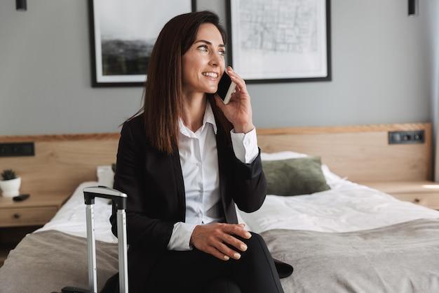 Piękny młody wesoły szczęśliwy biznes kobieta w wizytowym ubrania w pomieszczeniu w domu z walizką rozmawia przez telefon komórkowy.