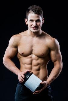 Piękny, młody, wysportowany mężczyzna trzyma słoik sportowego odżywiania