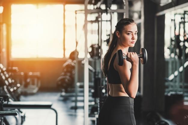 Piękny młody zdrowy kaukaski kobiety mienia dumbbell w gym