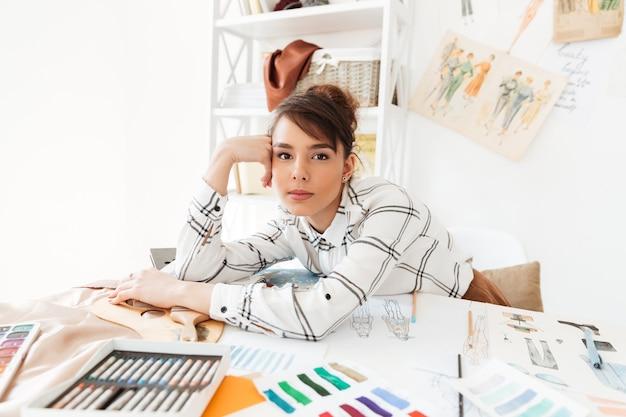 Piękny młody żeński projektanta mody obsiadanie przy jej pracy biurkiem