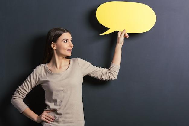 Piękny młody żeński uczeń trzyma żółtą mowę.