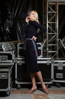 Piękny moda model w trykotowej sukni pozuje dla spojrzenie książki