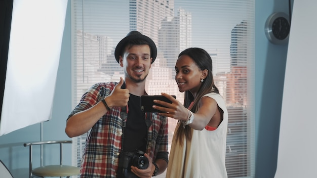 Piękny model afryki co selfie z przystojnym fotografem w profesjonalnym studio sesji zdjęciowej